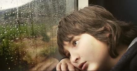 Sad child looking out rainy window.
